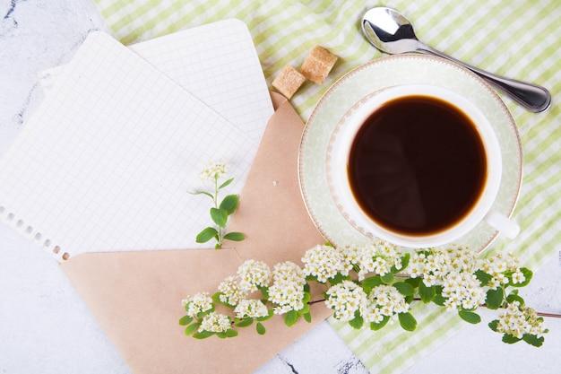 Thé dans une belle tasse blanche. enveloppe de courrier kraft avec des feuilles de papier. petit déjeuner. une branche de spirée en fleurs. concept japonais wabi sabi