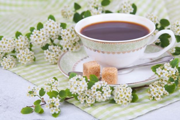 Thé dans une belle tasse blanche. petit déjeuner. une branche de spirée en fleurs. concept japonais wabi sabi