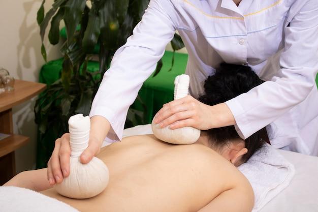 Thé dans des sachets de coton concept de massage. herbes au spa