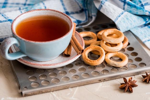 Thé dans une tasse bleue avec des biscuits, petit déjeuner de printemps sur un plateau d'époque
