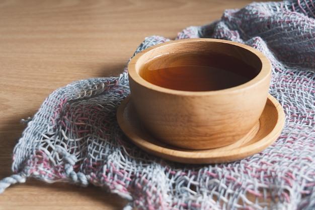 Thé dans une tasse en bois, placé sur un tissu tricoté à la main, idéal pour l'été