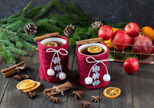 Thé dans une tasse avec un décor tricoté rouge, des tranches d'orange, un panier avec des fruits, de la cannelle, des branches d'épinette et des cônes