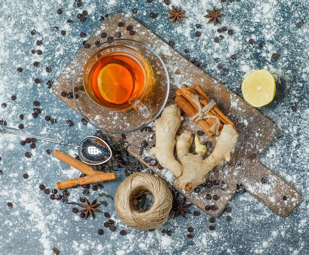 Thé dans une tasse avec farine, chips de choco, fil, passoire, épices, vue de dessus de citron sur béton et planche à découper