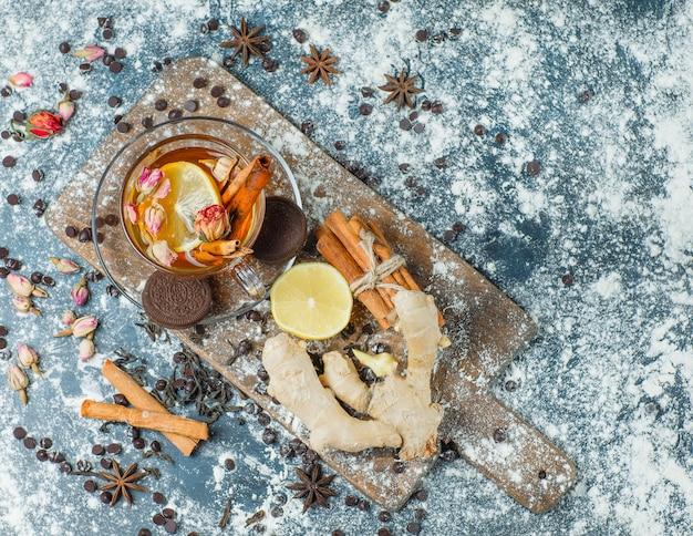 Thé dans une tasse avec farine, choco, biscuits, épices, citron, herbes vue de dessus sur béton et planche à découper