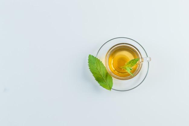 Thé dans une tasse avec des herbes à plat sur un fond blanc