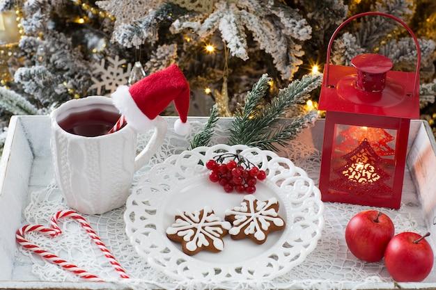 Thé dans une tasse, une lanterne, des pommes, des biscuits au pain d'épice et des bonbons