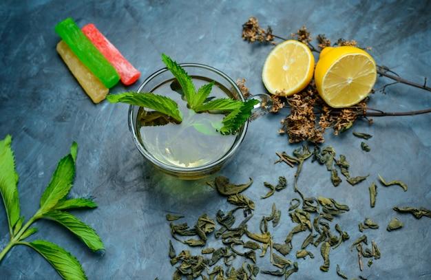 Thé Dans Une Tasse De Menthe, Herbes Séchées, Citron, Bonbons à Plat Posé Sur Une Surface Bleu Foncé Photo gratuit