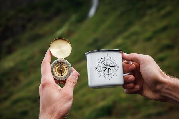 Thé dans une tasse en métal touristique et une boussole à la main fond naturel .vintage tone.