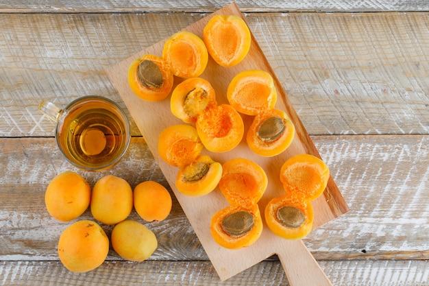 Thé dans une tasse en verre avec des abricots à plat poser sur une planche en bois et à découper