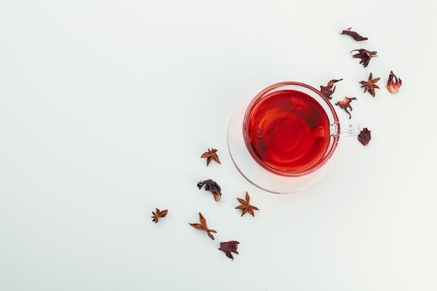 Thé dans une tasse en verre avec des épices et des herbes. vue de dessus.