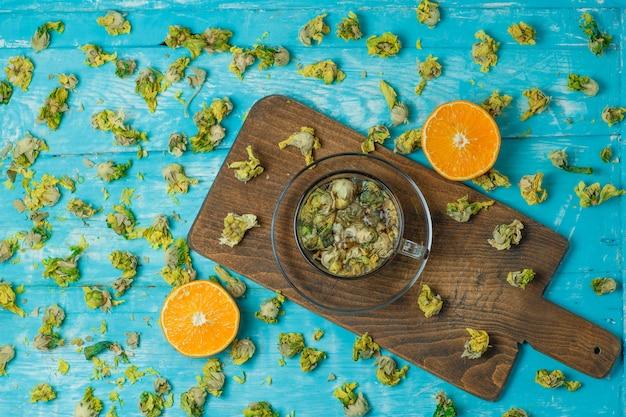 Thé dans une tasse en verre avec orange, herbes séchées vue de dessus sur planche à découper et bleu