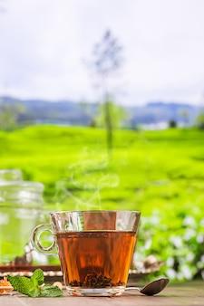Thé dans une tasse en verre sur la table en bois et la surface des plantations de thé
