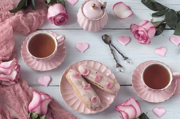 Thé dans des tasses roses, des cœurs roses en satin, deux éclairs à poisons et des roses roses