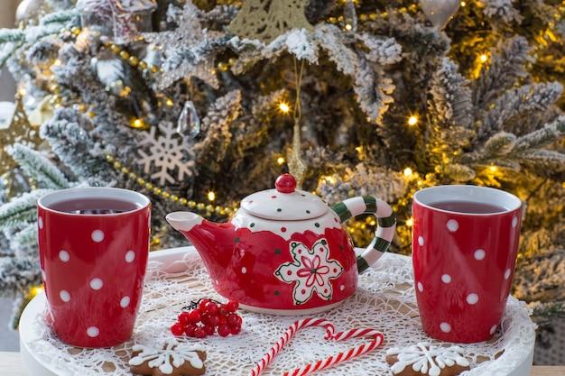 Thé dans des tasses, une théière, des biscuits au pain d'épice et des bonbons