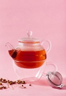 Thé dans une théière en verre sur un filtre infuseur rose et métal