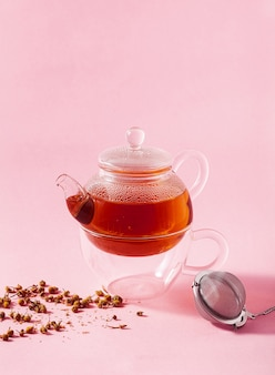 Thé dans une théière en verre sur fond rose et filtre infuseur en métal