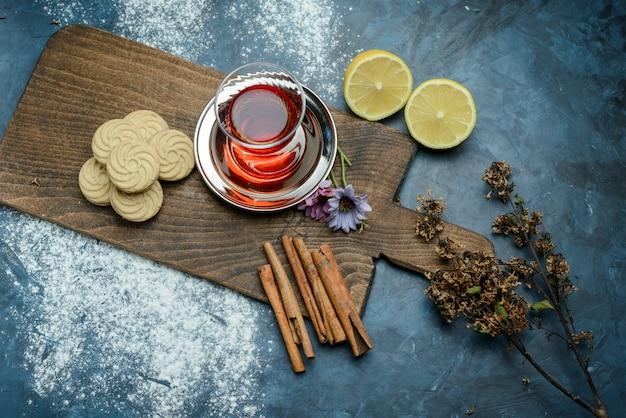 Thé dans un verre au citron, biscuits, herbes séchées, bâtons de cannelle, planche à découper vue de dessus sur la surface bleu grungy