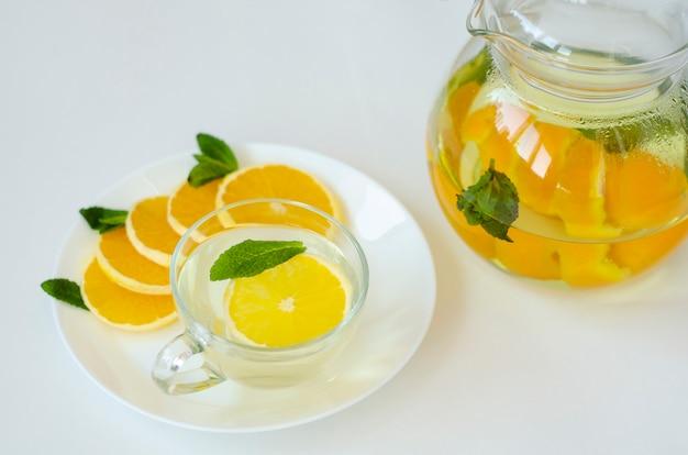 Thé detox dans une théière transparente à l'orange et à la menthe et à la fleur de narcisse jaune
