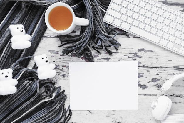 Thé et écharpe près de la feuille de papier et des appareils
