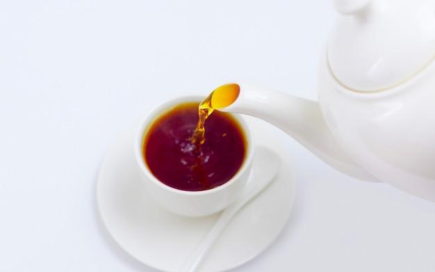 Le thé est versé dans une tasse blanche à partir d'une théière blanche sur fond blanc