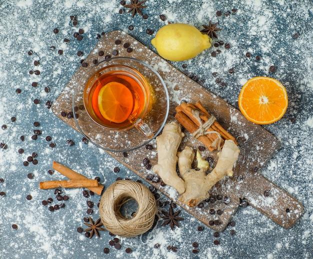Thé avec farine, chips de choco, fil, épices, orange, citron dans une tasse sur béton et planche à découper, vue de dessus.