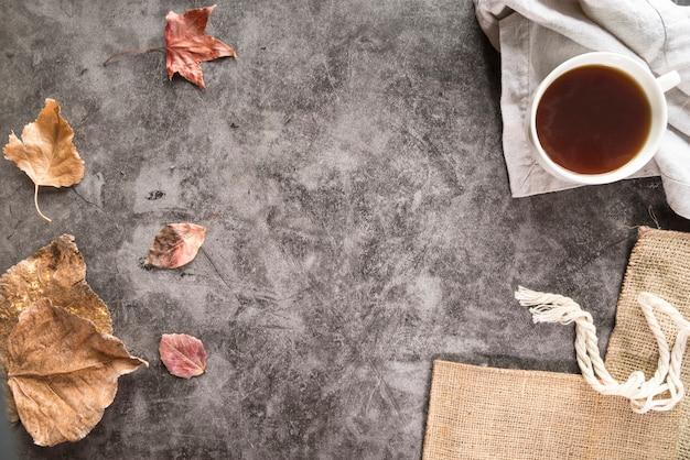 Thé et feuillage sec sur une surface minable