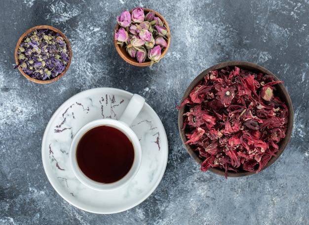 Thé et fleurs séchées sur table en marbre.
