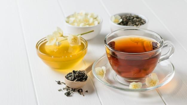 Thé fraîchement préparé avec des fleurs de jasmin et du miel sur une table rustique blanche.