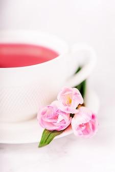 Thé à la framboise et fleurs de freesia rose sur un mur blanc, espace copie