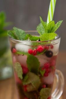 Thé de fruits frais aux fraises dans une coupe en verre, boisson de thé de fruits d'été, fond en bois.