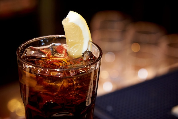 Thé glacé au citron dans un verre sur un arrière-plan flou foncé