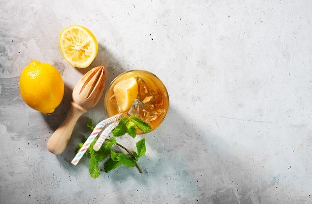 Thé glacé au citron sur fond gris béton avec menthe et glace