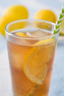 Thé glacé au citron sur une serviette de plage