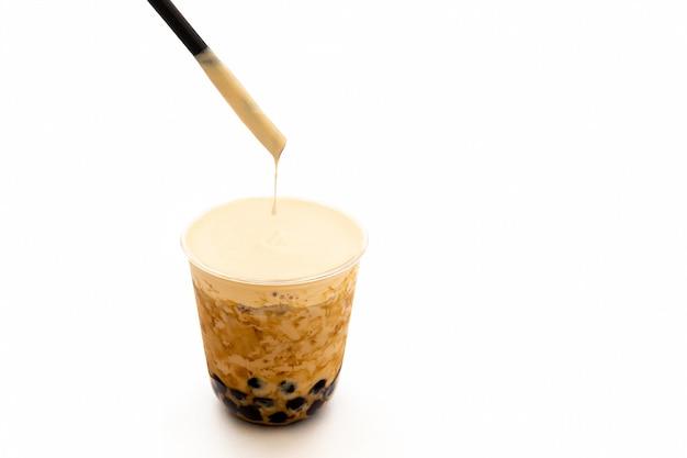 Thé glacé au lait perlé avec de la crème sur le dessus, isolé dans un tracé de détourage.