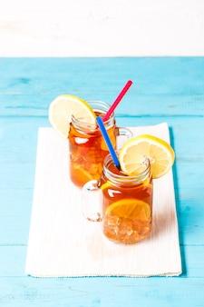 Thé glacé dans un bocal en verre avec du citron.