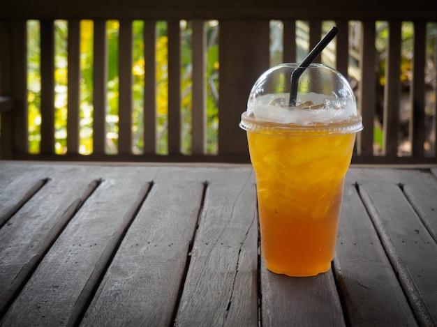 Thé glacé dans un verre en plastique avec de la paille