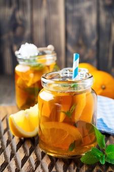 Thé glacé orange avec des feuilles de menthe dans un bocal en verre sur l'ancienne surface en bois