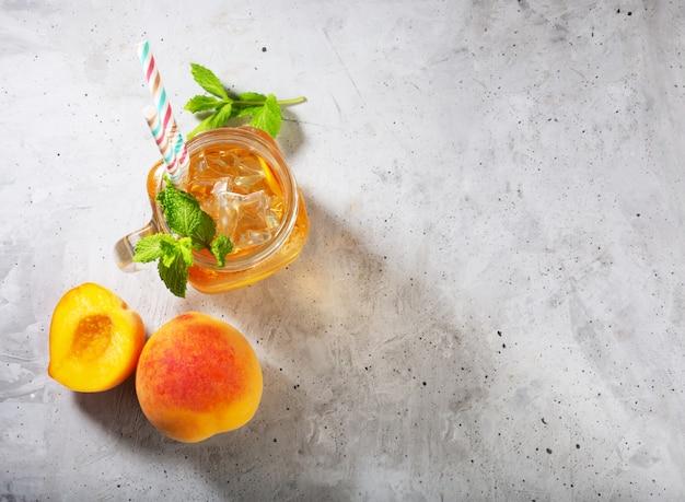 Thé glacé à la pêche sur fond gris béton avec menthe et glace, bonne boisson pour la saison chaude d'été
