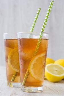 Thé glacé rafraîchissant au citron sur une table en bois blanc