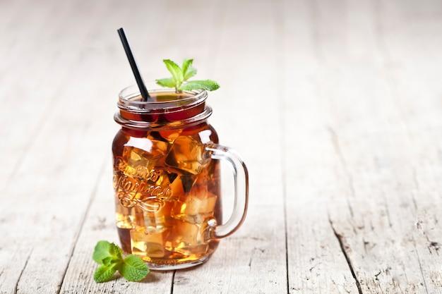 Thé glacé traditionnel au citron, feuilles de menthe et glaçons dans un bocal en verre