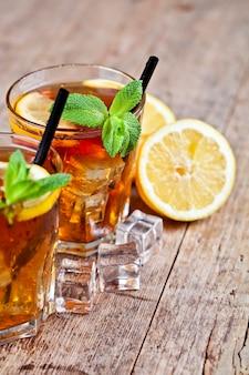 Thé glacé traditionnel au citron, feuilles de menthe et glaçons dans deux verres sur une table en bois rustique.