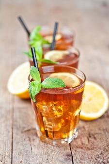 Thé glacé traditionnel au citron, feuilles de menthe et glaçons dans trois verres sur une table en bois rustique.