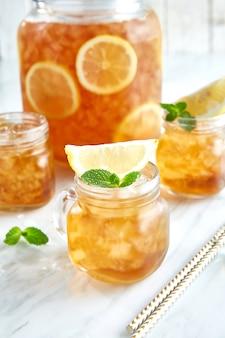 Thé glacé avec des tranches de citron et de menthe sur table
