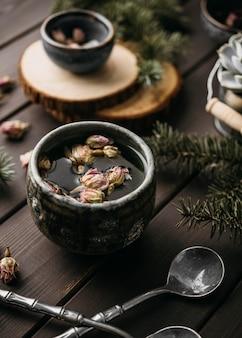 Thé à grand angle avec des fleurs séchées dans une tasse rustique