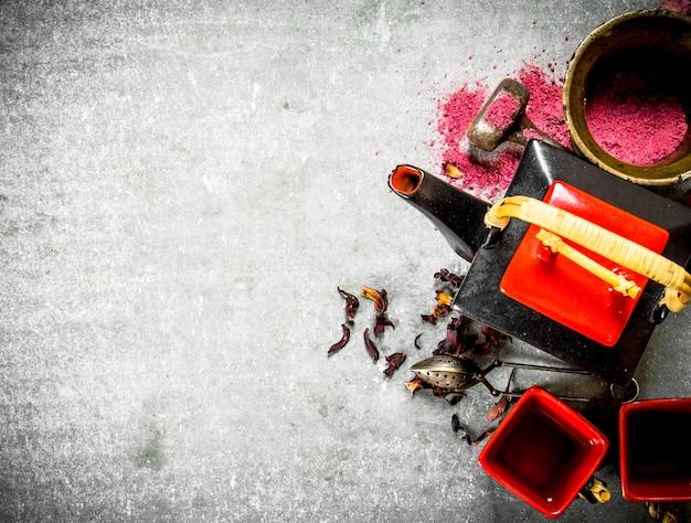Thé à la grenade écrasé dans un mortier sur table en pierre.