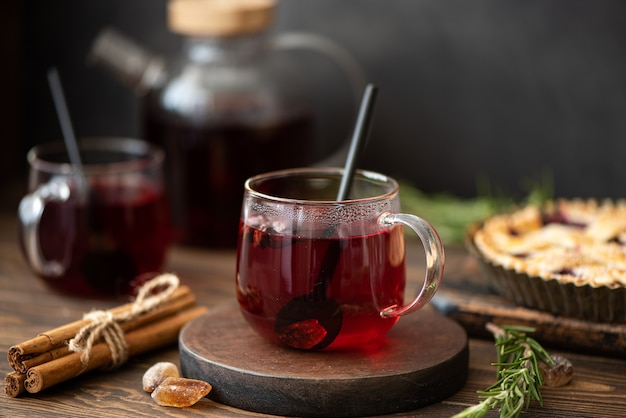 Thé d'hibiscus chaud avec de la cannelle et du sucre sur une table en bois