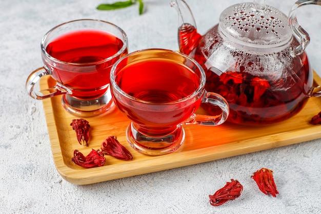 Thé à l'hibiscus chaud dans une tasse en verre et théière en verre.
