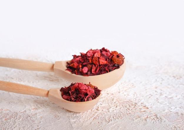 Thé d'hibiscus, raisins secs et abricots dans des cuillères en bois