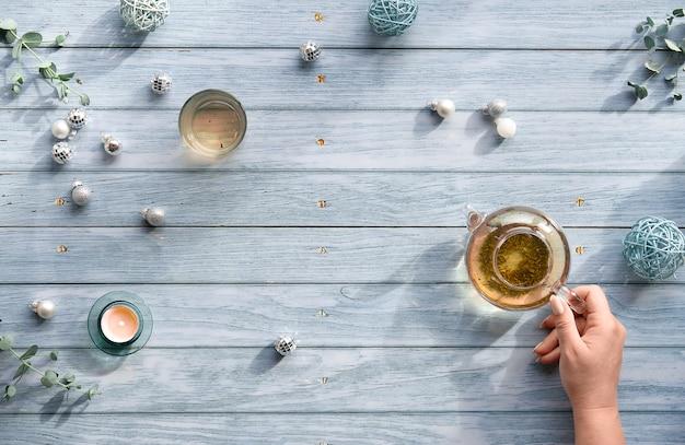 Thé d'hiver, arrangement plat avec théière en verre, verre de thé à la main sur des planches de bois bleu délavé.