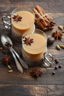 Thé indien masala chai. thé aux épices avec du lait dans les tasses vintage sur le tabl en bois rustique